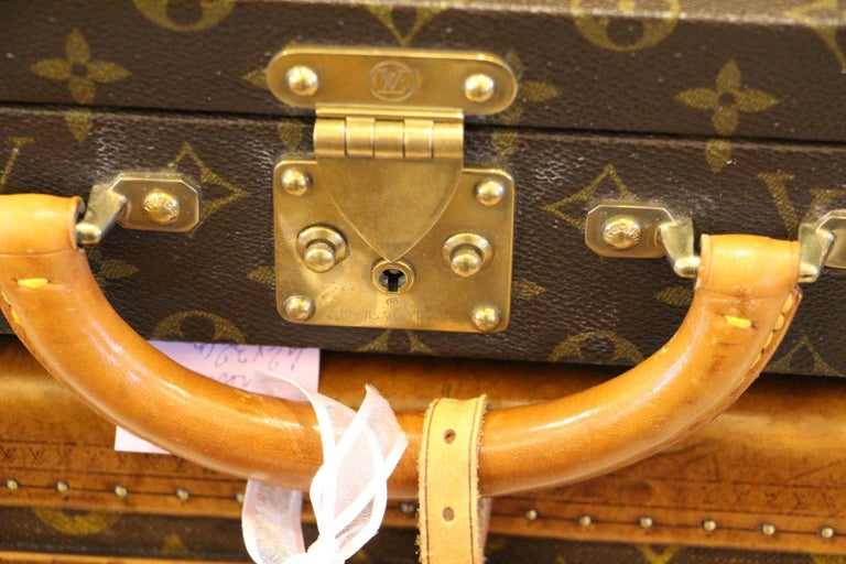 This elegant classeur briefcase features monogram canvas and a comfortable leather handle. Closed by a solid brass lock, it is accompanied by two crafted brass trunk latches. It has got its original keys. Green interior with two pockets under its