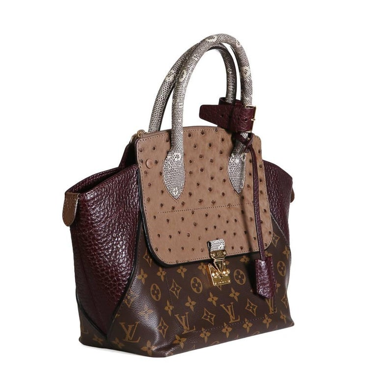 Special edition tote bag from Louis Vuitton Brown leather monogram body with ostrich panel and snakeskin handle Zip closure on top of the ostrich panels Front pouch with gold hardware squeeze lock, key included Maroon leather interior 16