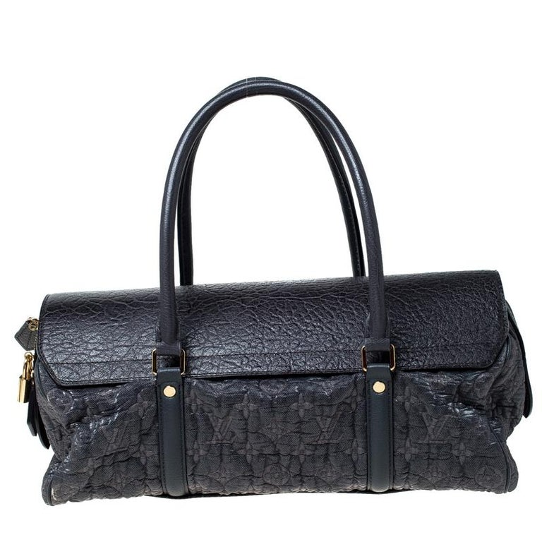 This bag is from Louis Vuitton's Fall/Winter 2010 Runway Collection. It is a limited edition piece made from monogram embossed jacquard canvas and detailed with a leather flap. On top, there are two handles and on the base, there are four metal