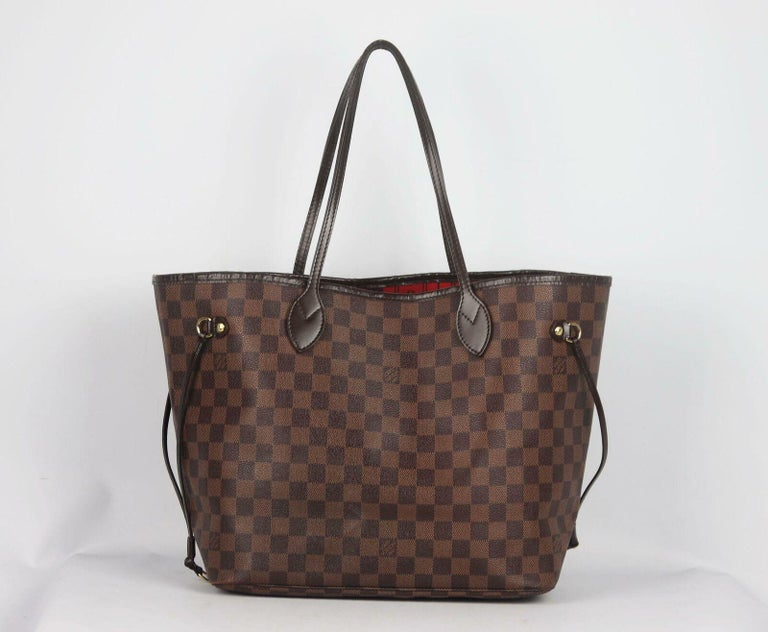 Louis Vuitton's classic 'Neverfall' bag in brown and beige Damier Ebène coated-canvas with leather accents, this 'MM' structured style has a spacious compartment lined in the brand's iconic red striped canvas with internal clip to attach your items
