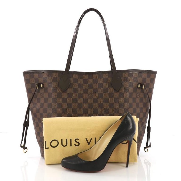 This Louis Vuitton Neverfull Tote Damier MM, crafted in damier ebene coated canvas, features dual slim handles, side laces, and gold-tone hardware. Its wide open top showcases a red striped fabric interior with side zip pocket. Authenticity code