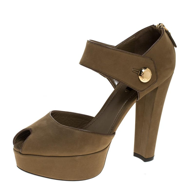 Wear these stylish sandals from the house of Louis Vuitton and channel your inner fashionista. Crafted in Italy, they are made from quality Nubuck leather. They come in a lovely shade of olive green. They are styled with peep toes, platforms, broad