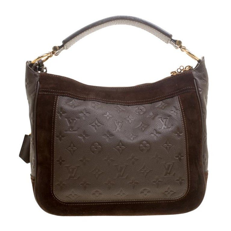 Flaunt this Louis Vuitton Audacieuse PM bag like a fashionista! Crafted from suede and monogram Empreinte leather, this bag was made in France and it features a top with double zippers that open to reveal a fabric-lined interior spacious enough to