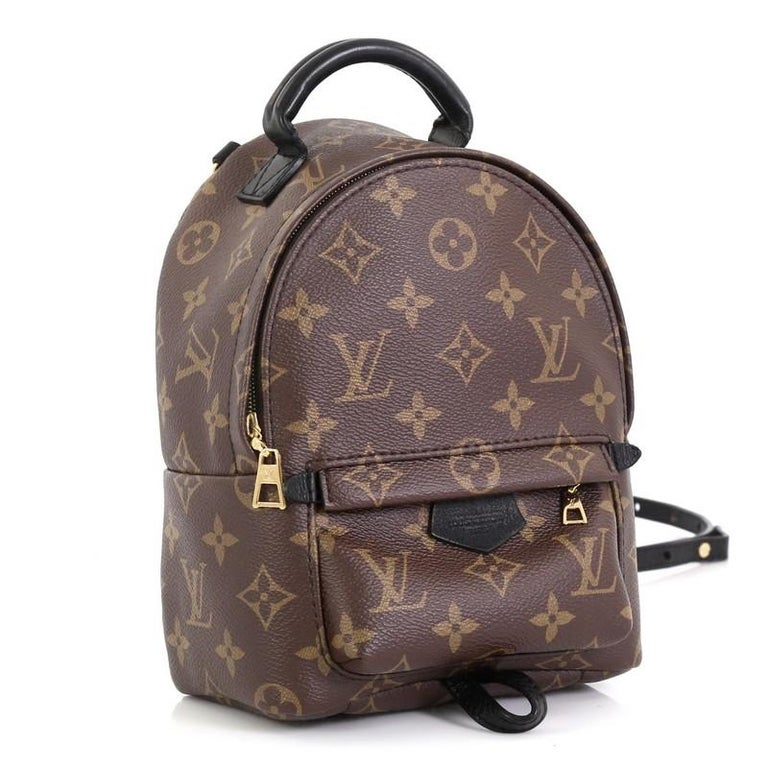 This Louis Vuitton Palm Springs Backpack Monogram Canvas Mini, crafted from brown monogram coated canvas, features a padded leather top handle, adjustable backpack shoulder straps, exterior front zip pocket, foam backing, and gold-tone hardware. Its