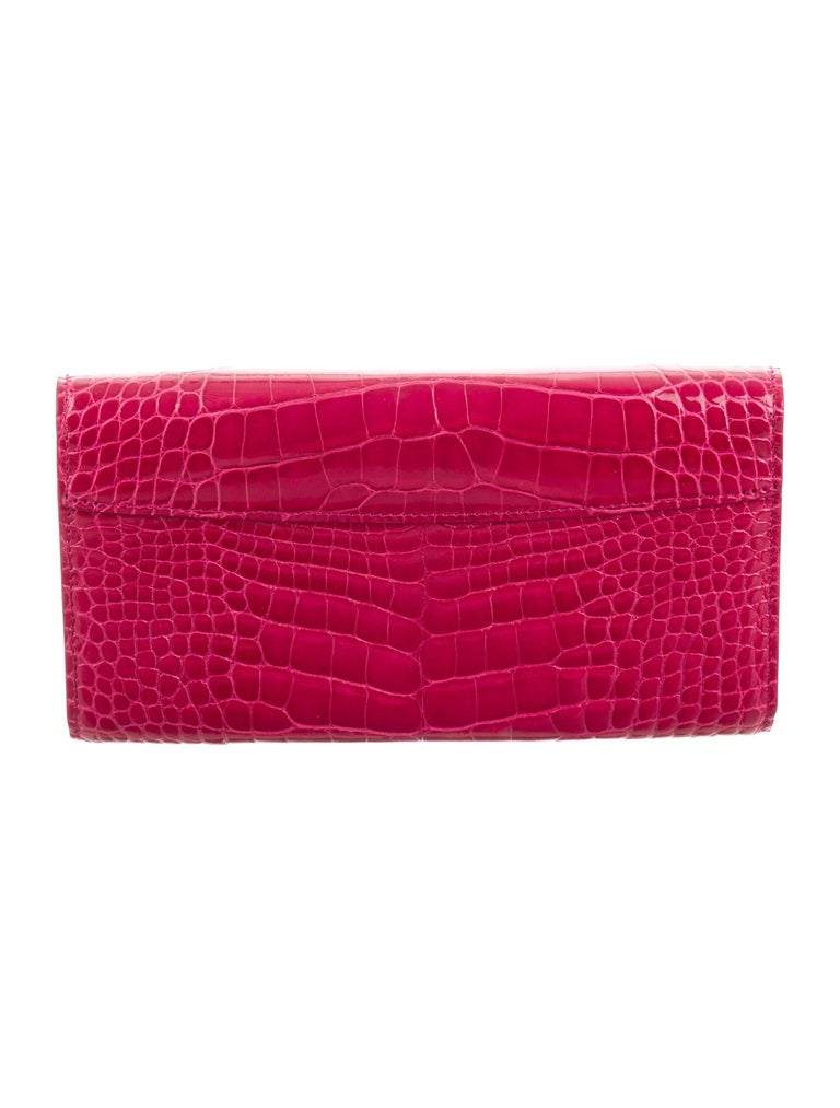 Crocodile Gold tone hardware Leather lining Snap closure  Features 12 interior card slots Measures 7.5