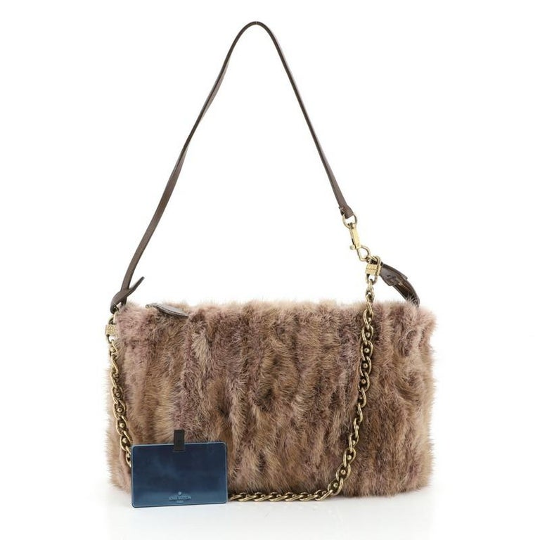 This Louis Vuitton Pochette Accessoires Limited Edition Caresse Mink, crafted from brown and pink mink, features chain link strap, flat leather strap and antique brass-tone hardware. Its zip closure opens to a black leather interior. Authenticity