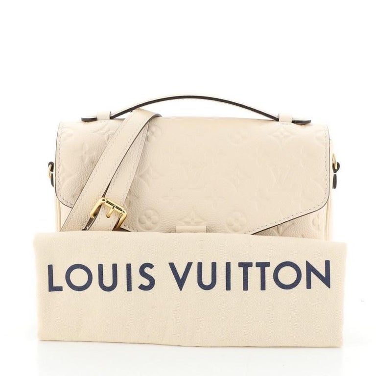 This Louis Vuitton Pochette Metis Monogram Empreinte Leather, crafted in neutral monogram empreinte leather, features a leather top handle, exterior back zip pocket, and gold-tone hardware. Its S-lock closure opens to a neutral fabric interior with