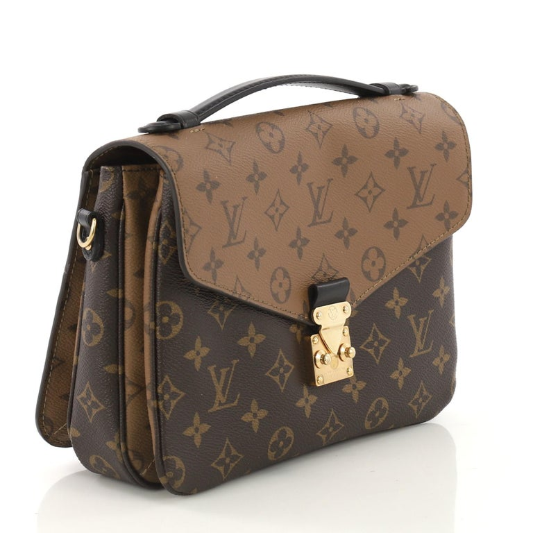 This Louis Vuitton Pochette Metis Reverse Monogram Canvas, crafted from brown reverse monogram coated canvas, features a top leather handle, exterior back zip pocket, and gold-tone hardware. Its s-lock closure opens to a black fabric interior