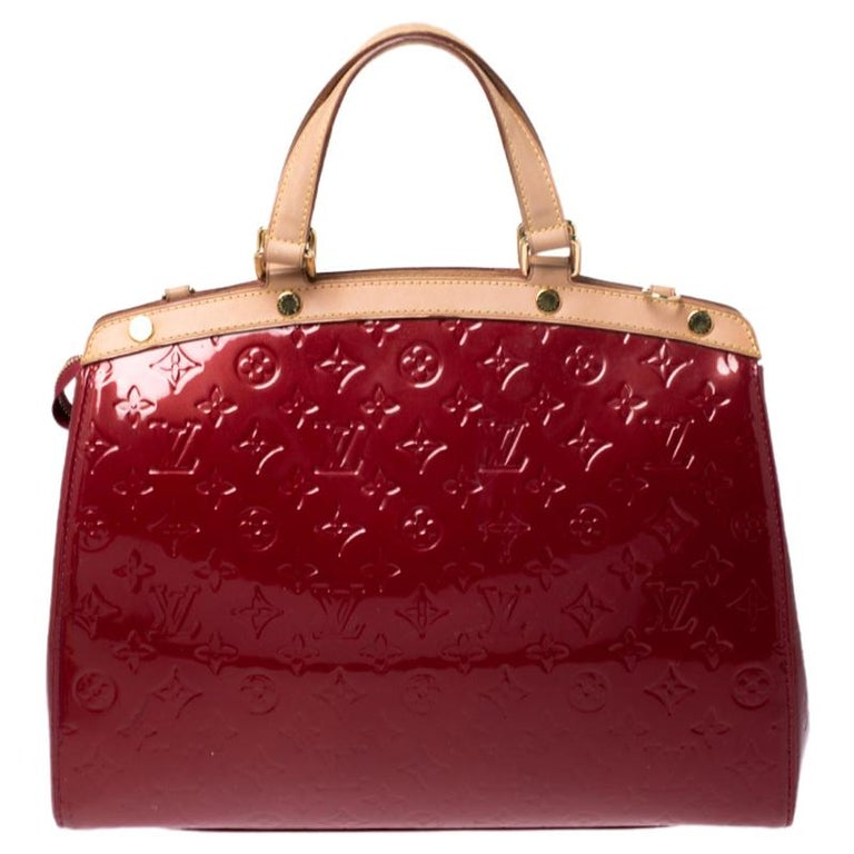 The feminine shape of Louis Vuitton's Brea is inspired by the doctor's bag. Crafted from Monogram Vernis in red, the bag has a perfect finish. The fabric interior is spacious and it is secured by a zipper. The bag features double handles, protective