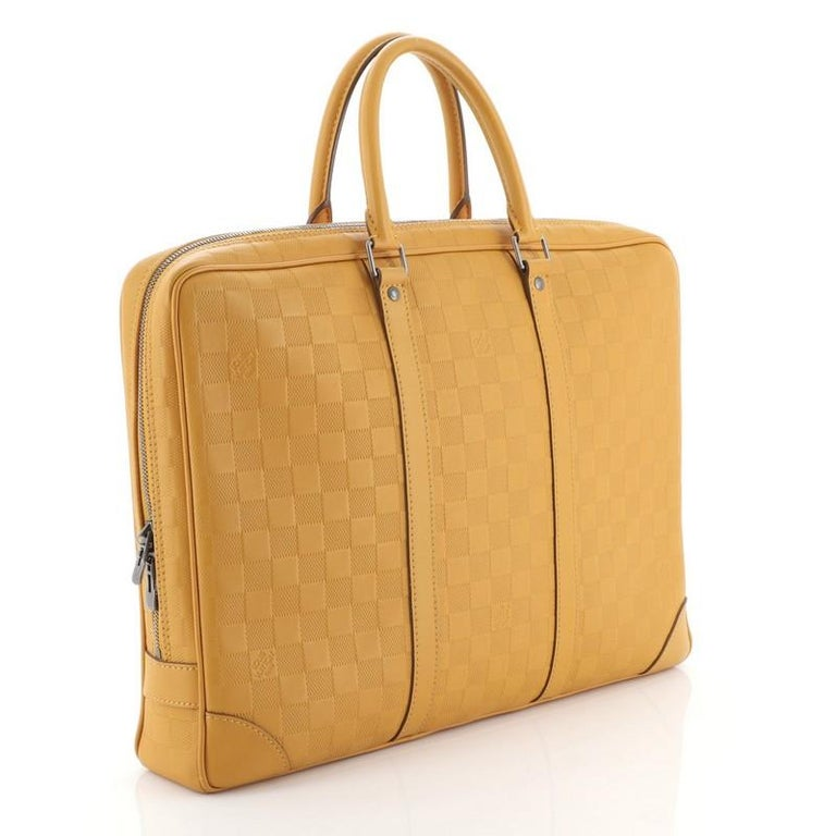 This Louis Vuitton Porte-Documents Voyage Briefcase Damier Infini Leather, crafted in orange damier infini leather, features dual rolled handles, leather base corners, and aged silver-tone hardware. Its top zip closure opens to a gray fabric