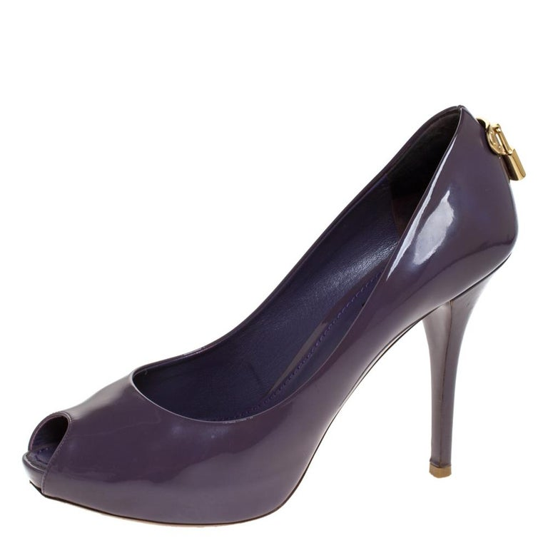 How splendid and glorious are these Oh Really! pumps from Louis Vuitton! Ravishing in purple, they come crafted from patent leather and feature a peep-toe silhouette. They flaunt an artistic engraved gold-tone padlock detailing on the counters and