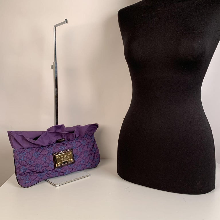 This beautiful Bag will come with a Certificate of Authenticity provided by Entrupy. The certificate will be provided at no further cost.  Beautiful Louis Vuitton 'Pochette Devi MM' clutch bag. Crafted from a purple nylon with embroidered LV symbols