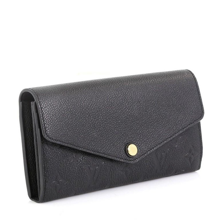 This Louis Vuitton Sarah Wallet NM Monogram Empreinte Leather, crafted from black monogram empreinte leather, features an envelope-style frontal flap and gold-tone hardware. Its snap button closure opens to a black leather interior with multiple