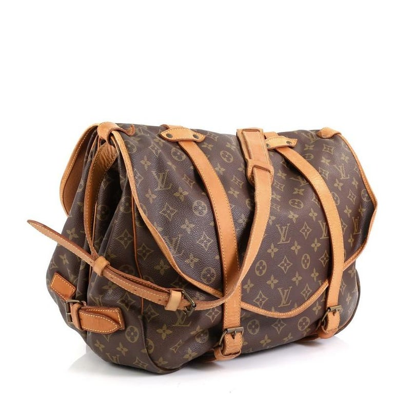 This Louis Vuitton Saumur Handbag Monogram Canvas 43, crafted in brown monogram coated canvas, features double saddle compartments with side buckle vachetta leather closures and gold-tone hardware. Its buckle closure opens to a brown fabric interior