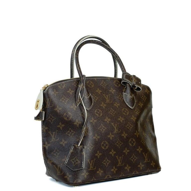 - Designer: LOUIS VUITTON - Model: shine fetish lockit - Condition: Very good condition.  - Accessories: Dustbag - Measurements: Width: 27,5cm , Height: 25cm, Depth: 14cm  - Exterior Material: Canvas - Exterior Color: Brown - Interior Material:
