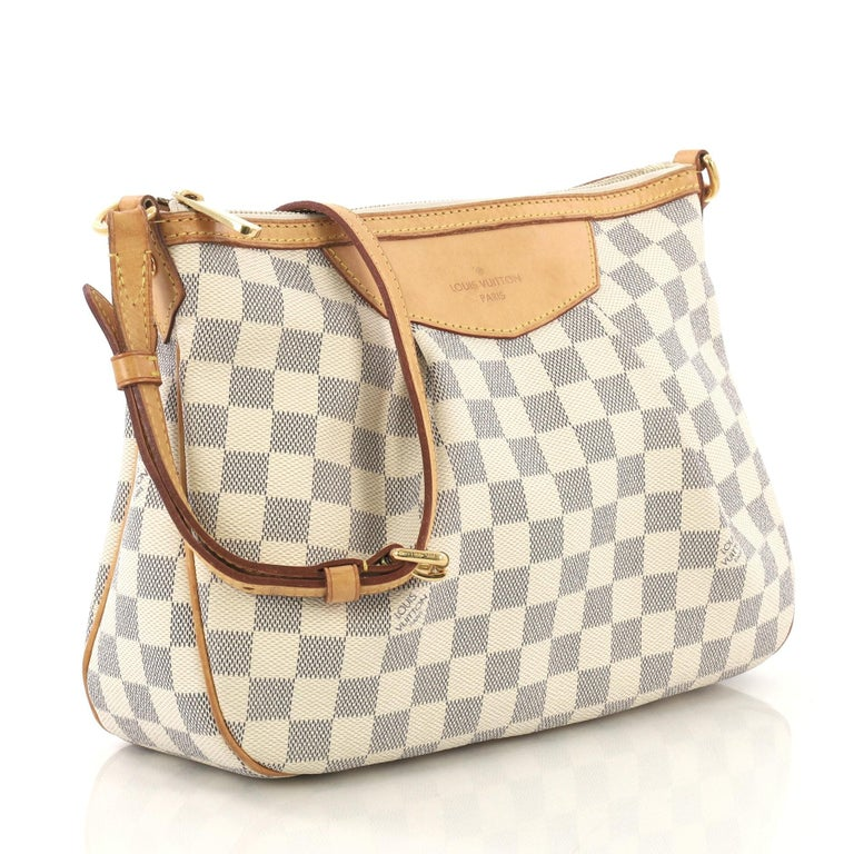 This Louis Vuitton Siracusa Handbag Damier PM, crafted in damier azur coated canvas, features a pleated silhouette, vachetta leather strap and trim, and gold-tone hardware. Its zip closure opens to a beige fabric interior with slip pocket.
