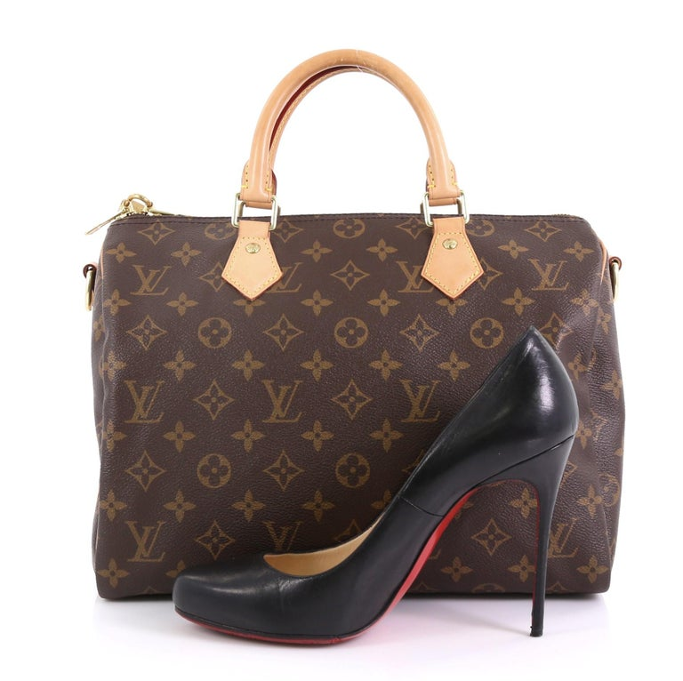 This Louis Vuitton Speedy Bandouliere Bag Monogram Canvas 30, crafted from brown monogram coated canvas, features dual rolled top handles and gold-tone hardware. Its zip closure opens to a brown fabric interior with side slip pocket. Authenticity
