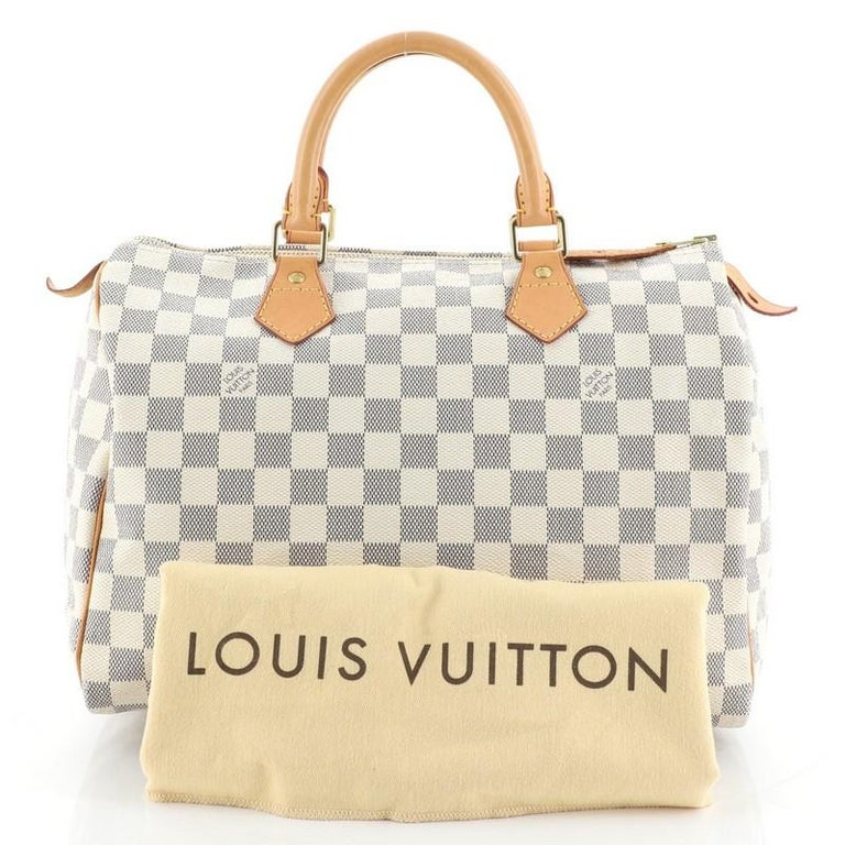This Louis Vuitton Speedy Handbag Damier 30, crafted in damier azur coated canvas, features dual rolled handles, leather trim, and gold-tone hardware. Its zip closure opens to a neutral fabric interior with zip pocket. Authenticity code reads: