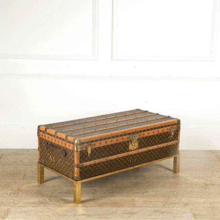An immaculate 1930s Louis Vuitton cabin steamer trunk. In excellent condition retaining its original tray and label. Now sitting on a solid brass custom made stand, ideal coffee table height.