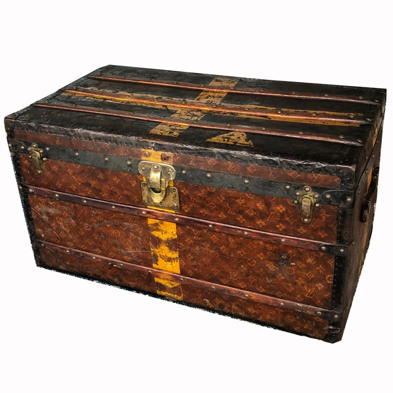 Authentic, antique Louis Vuitton monogram canvas steamer trunk from the early 20th C. Woven canvas, metal trim, leather handles with four wheels at the bottom. A key is included which still works to lock the primary latch. Three canvas & wood