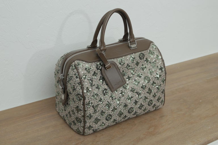 This Louis Vuitton Speedy is entirely covered in an embellishment of green sequin Louis Vuitton monogram on a beige tweed fabric background. This limited edition bag features two brown rolled leather top handles and leather trim with matte silver