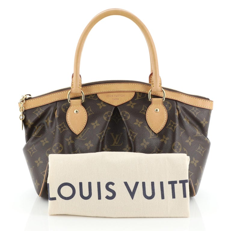 This Louis Vuitton Tivoli Handbag Monogram Canvas PM, crafted from brown monogram coated canvas, features dual rolled handles, subtle pleats in the middle, and gold-tone hardware. Its zip closure opens to a brown fabric interior with slip pockets.