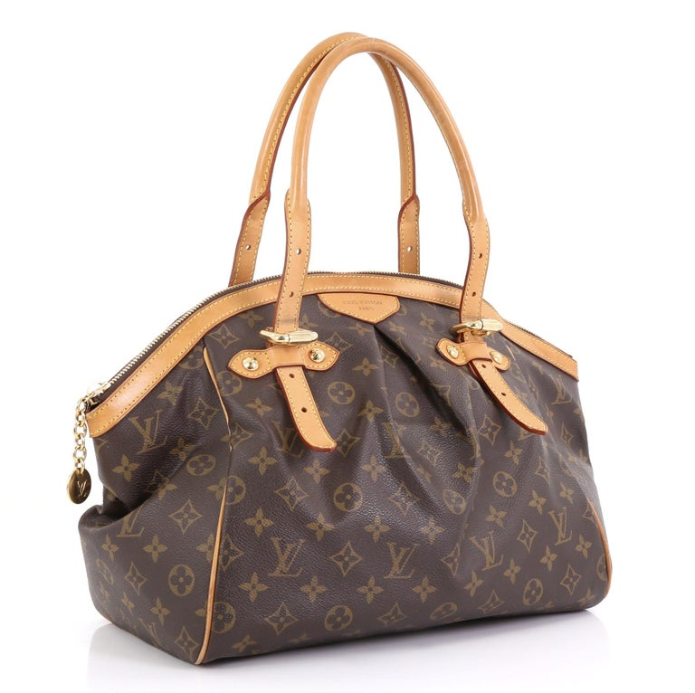 This Louis Vuitton Tivoli Handbag Monogram Canvas GM, crafted from brown monogram coated canvas, features dual rolled handles, subtle pleats in the middle, and gold-tone hardware. Its top zip closure opens to a brown fabric interior with slip