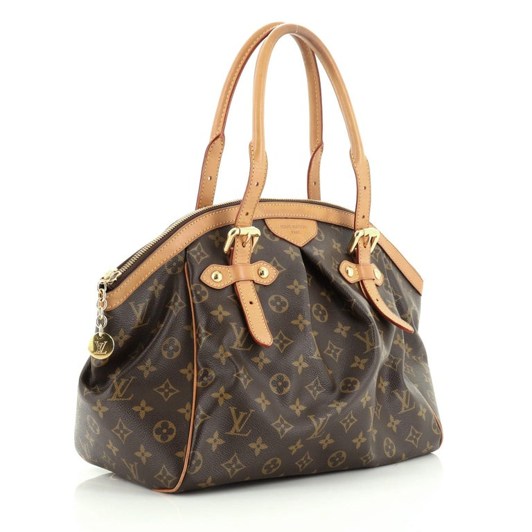 This Louis Vuitton Tivoli Handbag Monogram Canvas GM, crafted from brown monogram coated canvas, features dual rolled handles, subtle pleats in the middle, and gold-tone hardware. Its zip closure opens to a brown fabric interior with slip pockets.