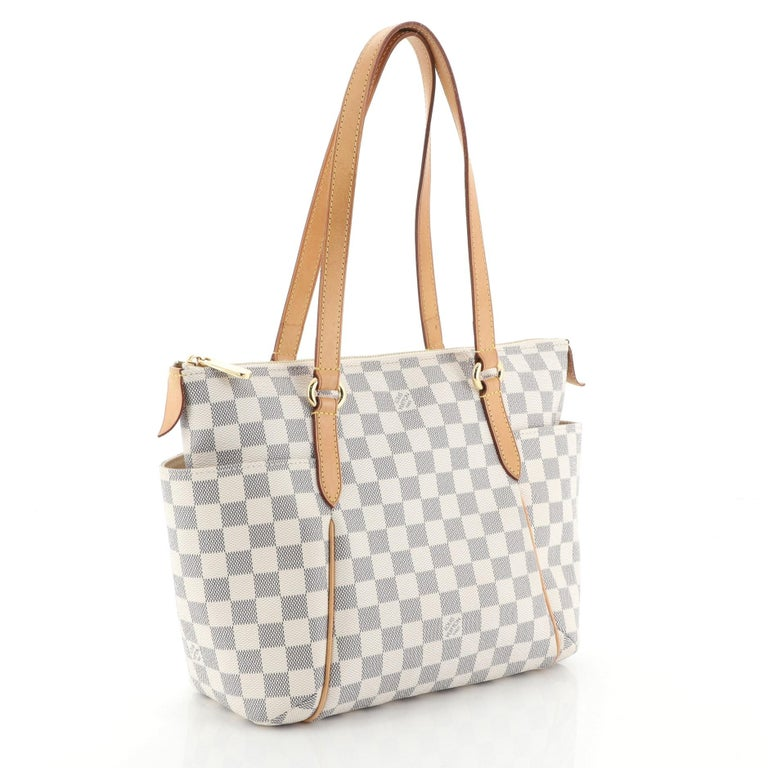 This Louis Vuitton Totally Handbag Damier PM, crafted from damier azur coated canvas, features tall cowhide leather handles and trim, two exterior lateral pockets, and gold-tone hardware. Its top zip closure opens to a neutral fabric interior with