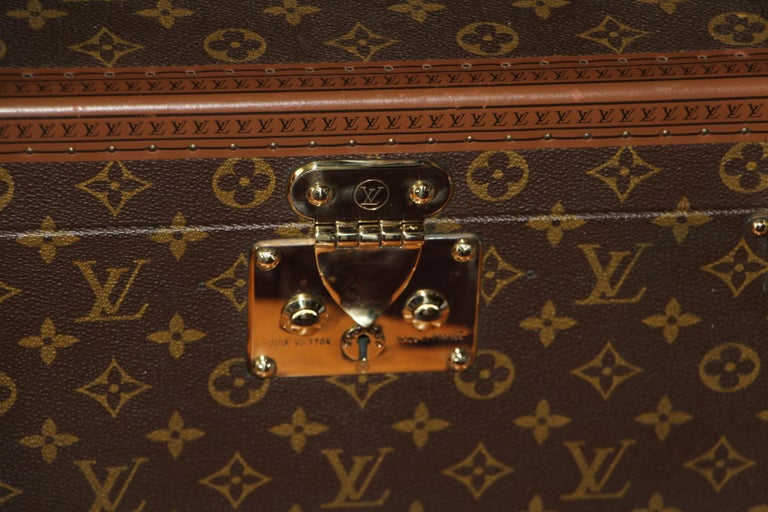 This beauty case features monogram canvas and all brass fittings. All studs are marked as well as its leather handle. Interior: beige coated canvas, adjustable leather straps for holding materials. Under its lid there is a mirror. Very clean and