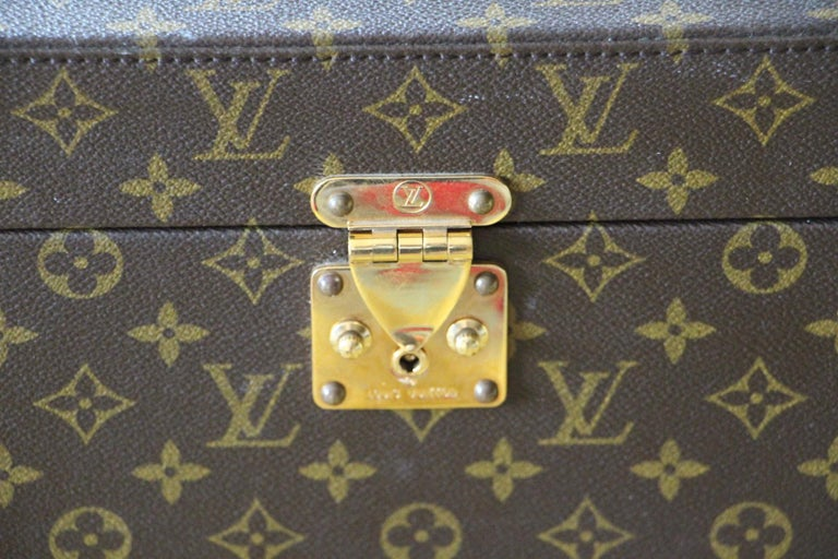 This rigid beauty case features monogram canvas and stamped Louis Vuitton brass lock. Its leather strap is adjustable and is also marked Louis Vuitton. Interior, beige canvas, leather straps for holding materials. Under its lid there is a mirror.