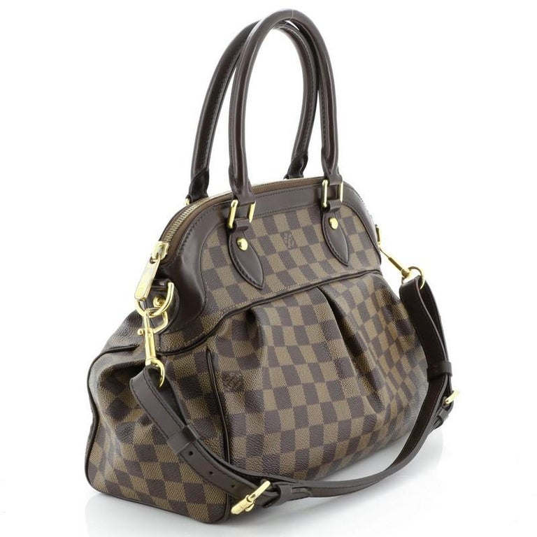 This Louis Vuitton Trevi Handbag Damier PM, crafted from damier ebene coated canvas, features dual rolled handles, leather trim, and gold-tone hardware. Its zip closure opens to a red microfiber interior with slip pockets. Authenticity code reads:
