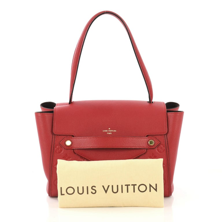 This Louis Vuitton Trocadero Handbag Monogram Empreinte Leather, crafted from red monogram empreinte leather, features a looping top handle, subtle LV logo at front, protective base studs, and gold-tone hardware. Its hidden magnetic closure opens to