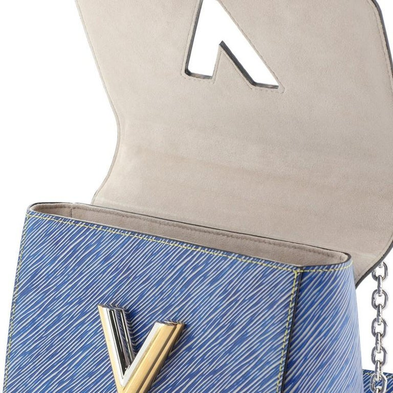 This Louis Vuitton Twist Handbag Epi Leather MM, crafted from blue epi leather, features chain link strap with leather pad, frontal flap, and silver-tone hardware. Its LV twist lock closure opens to a gray microfiber interior with slip pockets.