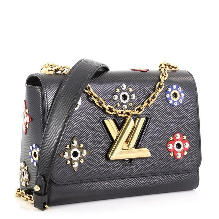 This Louis Vuitton Twist Handbag Limited Edition Mechanical Flowers Epi Leather MM, crafted from black epi leather, features chain link strap with leather pad, multicolor flowers with circular studs, and gold and silver-tone hardware. Its LV