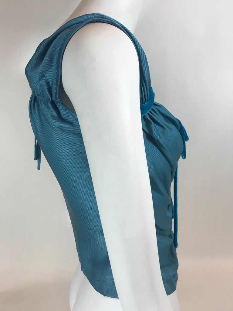 Medium teal blue sleeveless top with V-neck featuring velvet tie accents at front, and zip closure at back.