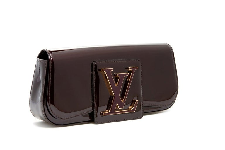 Amarante patent Vernis Louis Vuitton sobe clutch with over sized Louis Vuitton logo on the front and a magnetic snap closure. Height: 5 inches Length: 10 inches Width: 2 inches