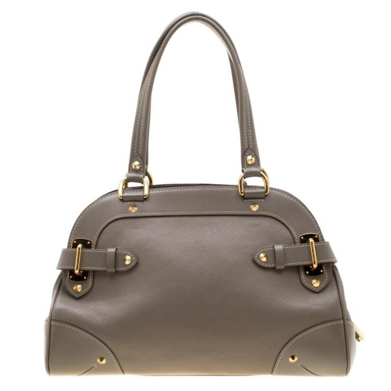 This Le Radieux bag from Louis Vuitton is gorgeous. The grey beauty is crafted from leather and flaunts a unique and distinctive style. It features beautiful gold-tone studs, buckles, and the lock accent all of which shine to make it an enchanting