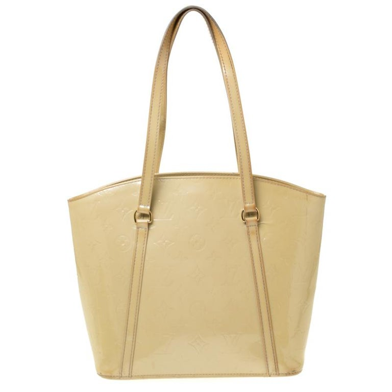 Spacious and high on style, Louis Vuitton's Avalon has a feminine look. Crafted from beige Monogram Vernis patent leather, the bag features dual top handles and gold-tone hardware. The open top reveals a fabric-lined interior that is spacious enough
