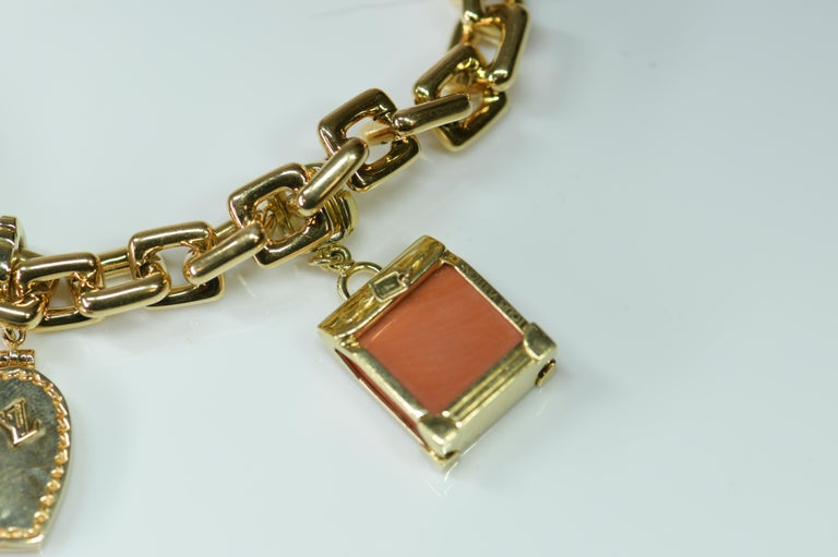A wonderful authentic Louis Vuitton 18K yellow gold and charm bracelet, four assorted detachable and gem-set charms including a coral steamer, a gold heart shape locket, a gold padlock, and a pair of gold keys. Bracelet and each charm with maker's