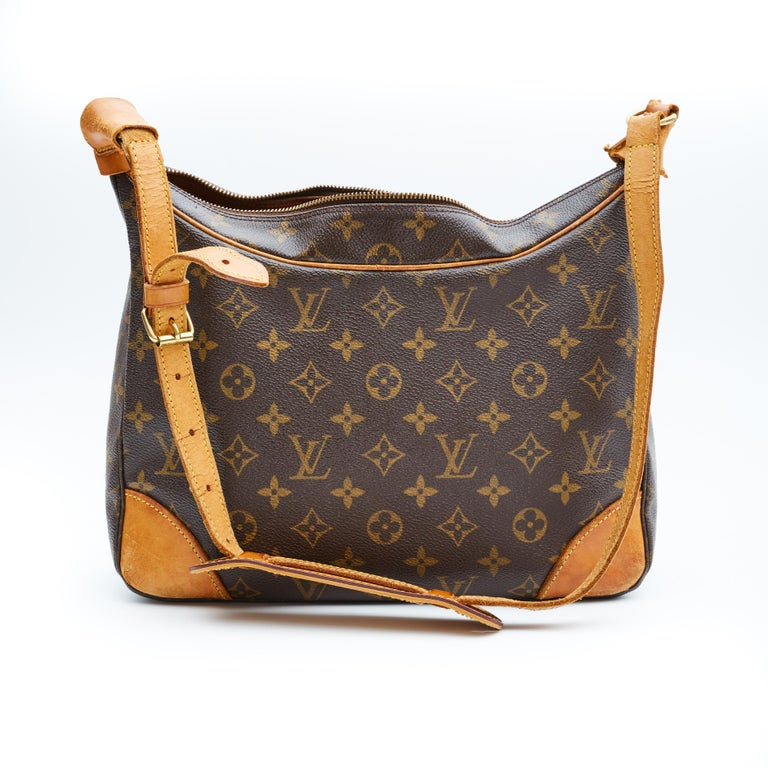 This shoulder bag is made with brown monogram on toile canvas with aged vachetta cowhide leather on the shoulder strap, base corners and trim. The bag features brass hardware, top zip closure and terra-cotta cross grain leather interior lining with