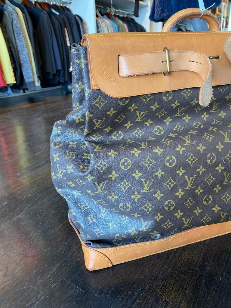 Brown and tan monogram print coated canvas. Brass hardware. Turn-lock closure with dual additional pull-through closures at flap. Single rolled top handle. Tan Vachetta trim. Light brown woven lining.   *Note* - Lock is on closure and there is no