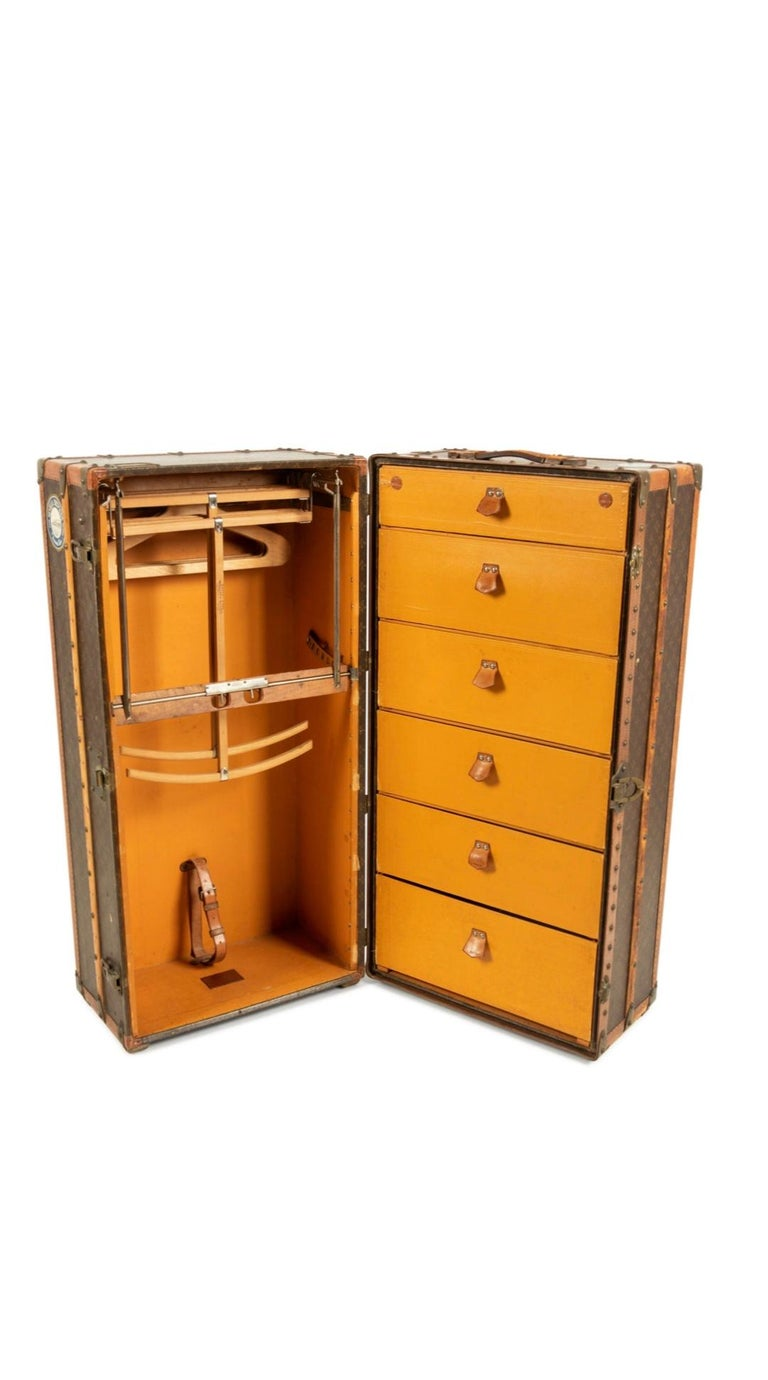 Louis Vuitton Wardrobe Steamer trunk, early 20th century  Wardrobe trunk covered in monogram canvas with natural Lozine leather trim and handles, and brass hardware with front lock and key. The interior has wood LV hangers and dust ruffle on