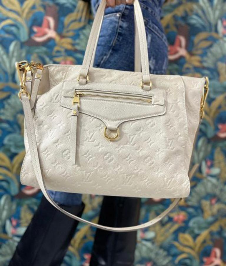 Louis Vuitton bag Ombre Lumineuse model Empreinte line made of white monogram leather with golden hardware. It has a zip closure, very large inside and equipped with pockets. The bag has a double handle and a removable shoulder strap. It is in