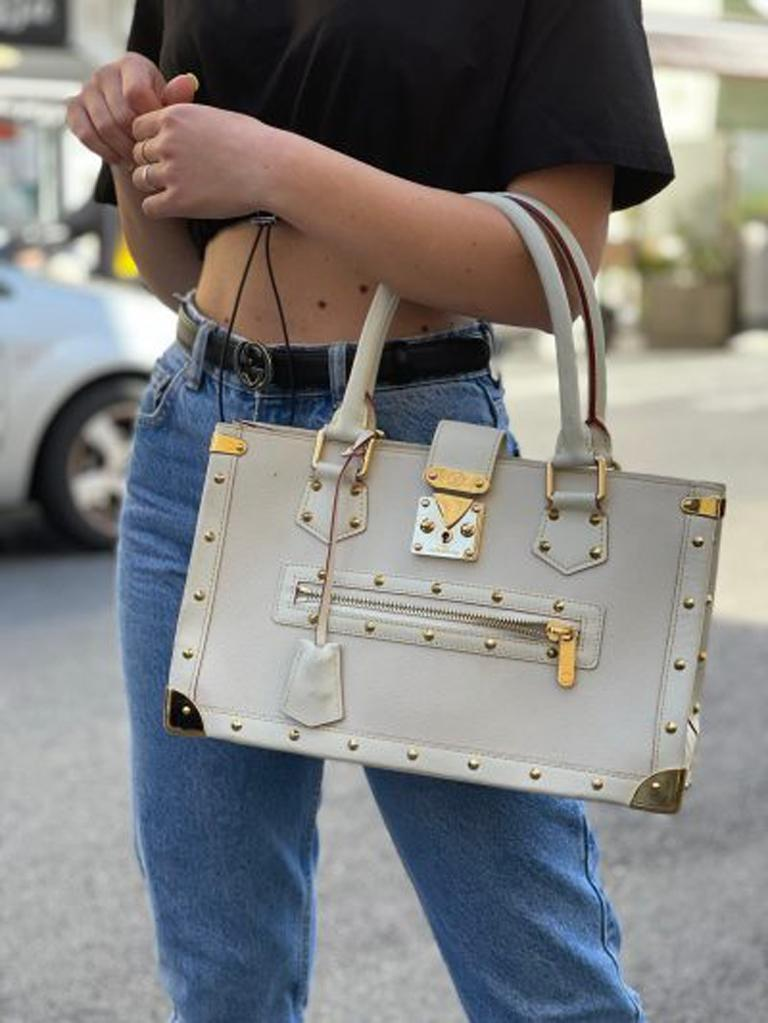 """This elegant Louis Vuitton bag is made of white goat leather and gold tone metallic finishes. Its exterior is embellished with golden studs, protective metal corners and an """"S"""" snap closure. Externally it has a comfortable front pocket with zip, two"""
