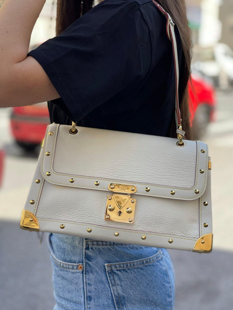 Louis Vuitton signed bag, Suhali Le Talentueux model, made of white leather with golden hardware. Equipped with an interlocking closure, internally lined in white fabric, quite roomy. Equipped with a 3 cm thick adjustable shoulder strap and an