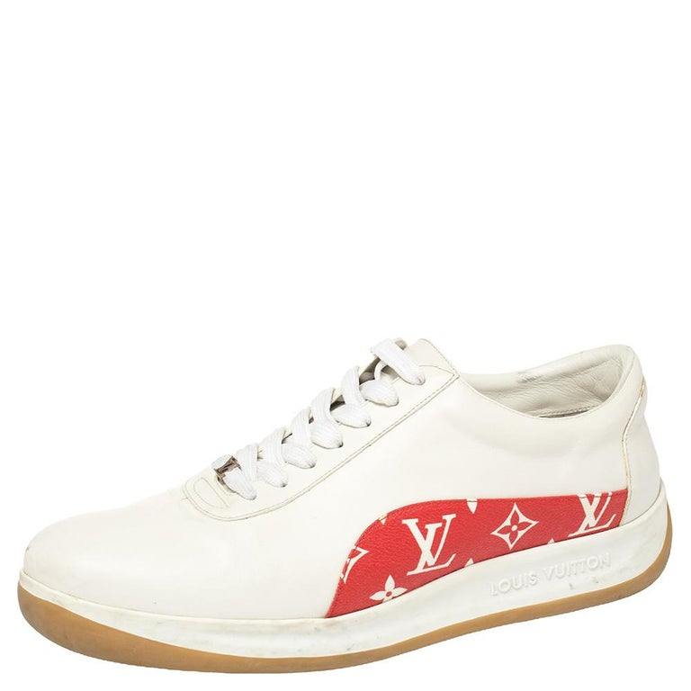These Louis Vuitton x Supreme sneakers are fashioned in classic white leather with an appealing monogram canvas trim in a contrasting red hue accented on the quarters. They feature a lace-up silhouette with the brand logo and leather lining on the