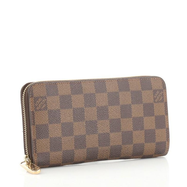 This Louis Vuitton Zippy Wallet Damier, crafted from damier ebene coated canvas, features gold-tone hardware. Its all-around zip closure opens to a brown leather interior with multiple card slots, two gusseted open pockets, and zip pocket.