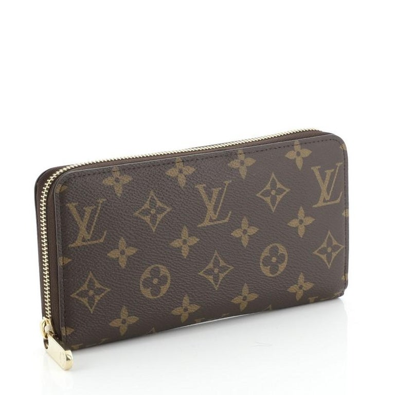 This Louis Vuitton Zippy Wallet Monogram Canvas, crafted from brown monogram coated canvas, features gold-tone hardware. Its all-around zip closure opens to a brown leather interior with multiple card slots, slip pocket, and zip compartment.
