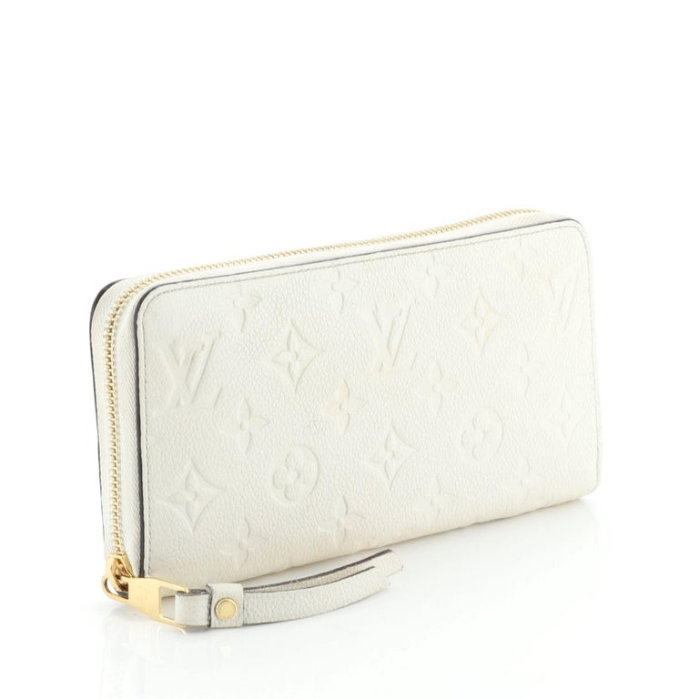 This Louis Vuitton Zippy Wallet Monogram Empreinte Leather, crafted in white monogram empreinte leather, features gold-tone hardware. Its all-around zip closure opens to a white leather interior with a middle zip compartment, slip pocket, and